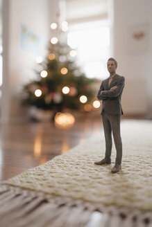 Businessman figurine standing next to a Christmas tree at home - FLAF00150