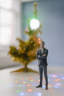 Businessman figurine standing next to a Christmas tree at home - FLAF00159