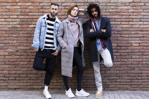 Portrait of three serious friends standing at a brick wall - JRFF02614
