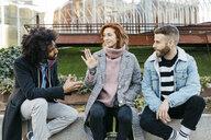 Three friends sitting in the city talking - JRFF02623