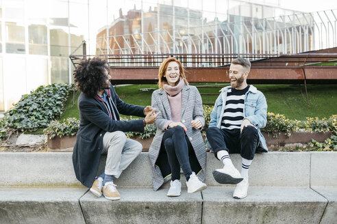 Three happy friends sitting in the city talking - JRFF02626