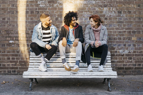 Three friends talking on a bench in front of a brick wall - JRFF02632