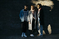 Three serious friends standing at a brick wall in shadow - JRFF02635
