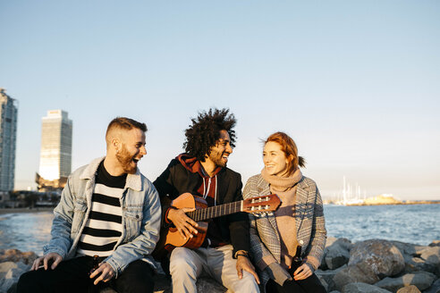 Three happy friends with guitar sitting outdoors at the coast sunset - JRFF02659