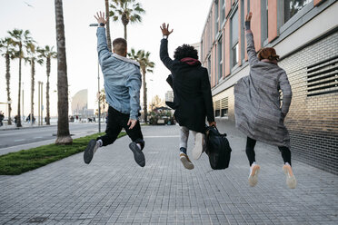 Rear view of three friends jumping in the city - JRFF02662