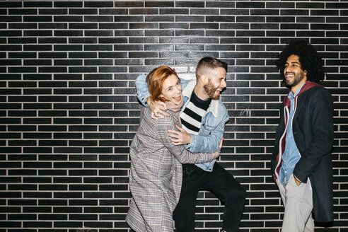 Spain, Barcelona. Three real friends at night so happy with a black wall in the background. - JRFF02668
