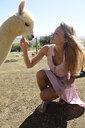Blond mature woman stroking young alpaca - ECPF00489