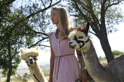 Blond woman with two leashed alpacas in nature - ECPF00492