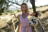 Portrait of smiling blond woman with two leashed alpacas - ECPF00495