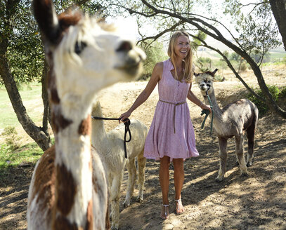 Happy blond woman with alpacas - ECPF00498