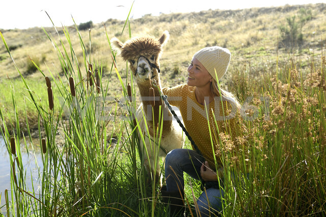 Smiling mature woman with leashed alpaca in nature - ECPF00513 - Eyecatcher.pro/Westend61