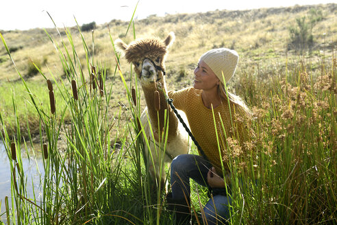 Smiling mature woman with leashed alpaca in nature - ECPF00513
