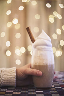 Hand holding coffee with cream, bokeh lights on the background - EPF00554