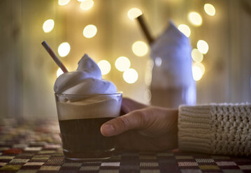 Hand taking coffee with cream, bokeh lights on the background - EPF00557