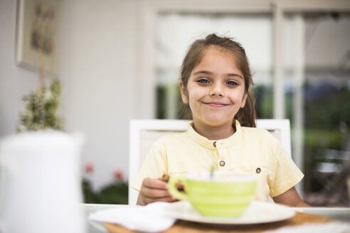 Portrait of smiling little girl having breakfast at home - ABZF02225