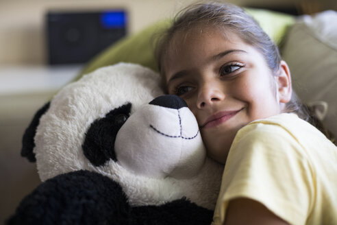 Beautiful girl smiling embracing a teddy panda bear on a sofa in home in Madrid, Spain. - ABZF02240