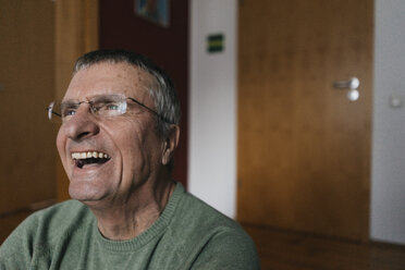 Laughing senior man at home looking away - KNSF05506