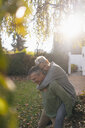 Happy senior man carrying wife piggyback in garden - KNSF05509