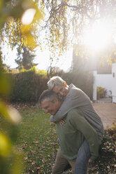 Happy senior man carrying wife piggyback in garden - KNSF05509