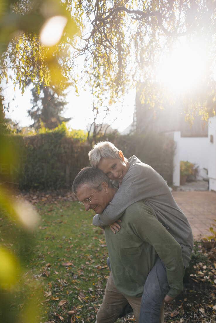 Happy senior man carrying wife piggyback in garden - KNSF05509 - Kniel Synnatzschke/Westend61