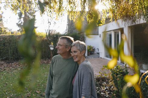 Happy senior couple in garden looking around - KNSF05512