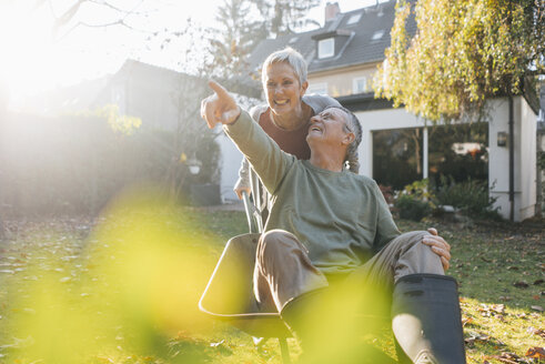 Happy senior couple having fun with wheelbarrow in garden - KNSF05515