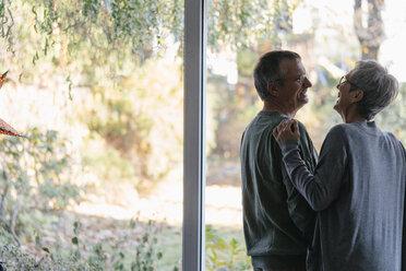 Happy senior couple standing at panorama window - KNSF05521