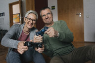 Happy senior couple playing video game at home - KNSF05548