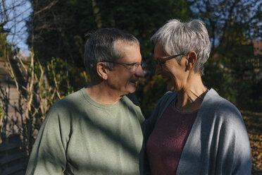 Affectionate senior couple facing each other in garden - KNSF05554