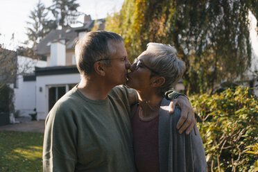 Affectionate senior couple embracing and kissing in garden - KNSF05557