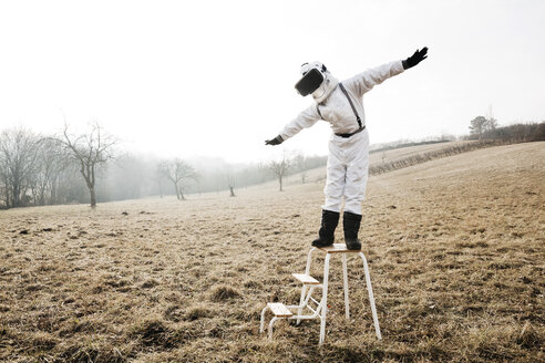 six year old cool boy wearing white space suit ist posing outdoor in a meadow, sometimes with virtual reality glasses - HMEF00204