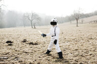 Boy wearing white space suit with sword pon on a meadow with virtual reality glasses - HMEF00207