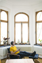 Casual man in yellow shirt with headphones sitting in Lounge Chair in stylish apartment - SBOF01723