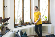 Pensive man in yellow shirt in stylish apartment looking out of window - SBOF01726