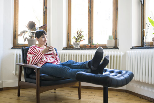 Short-haired woman relaxing in lounge chair holding coffee mug in stylish apartment - SBOF01729