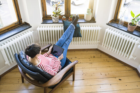 short-haired woman relaxing in lounge chair holding tablet in stylish apartment - SBOF01732