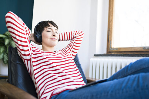 Short-haired woman with headphones relaxing in lounge chair - SBOF01735