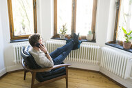 Casual man sitting in Lounge Chair in stylish apartment talking on the phone - SBOF01738