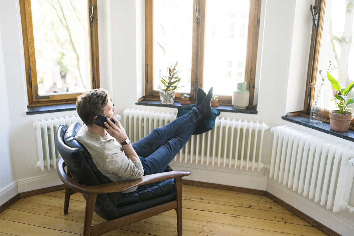 Casual man sitting in Lounge Chair in stylish apartment talking on the phone - SBOF01738 - Steve Brookland/Westend61