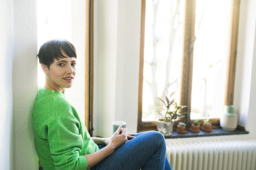 Portrait of short-haired woman with green pullover sitting at window in stylish apartment with coffeee mug - SBOF01741