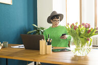 Businesswoman in home office working at her laptop and looking on her phone - SBOF01747