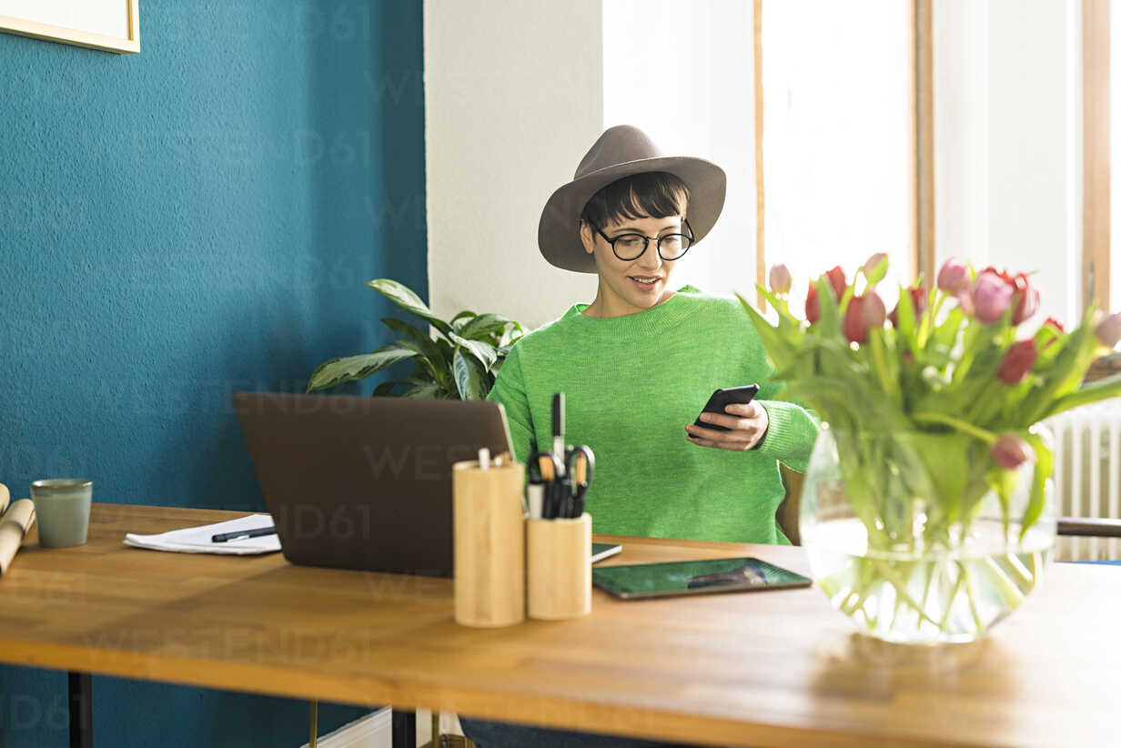Businesswoman in home office working at her laptop and looking on her phone - SBOF01747 - Steve Brookland/Westend61