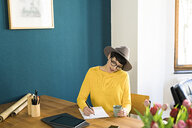 Businesswoman in home office writing on a piece of paper holding coffee mug - SBOF01753