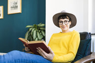 Portrait of smiling woman relaxing in lounge chair reading a book - SBOF01768