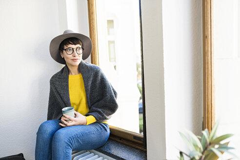Woman sitting on windowsill looking outside holding coffee mug - SBOF01771