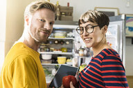 Portrait of couple with tablet in front of their fridge doing online shopping for groceries - SBOF01783