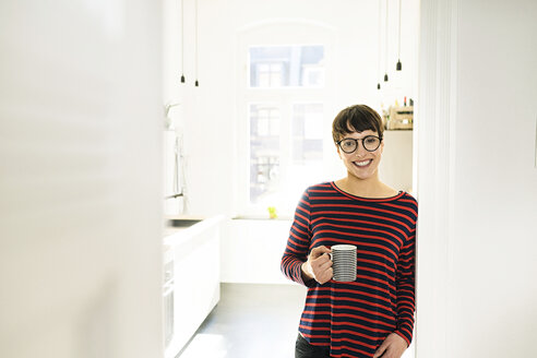 confident short-haired woman with coffee mug leaning on door frame - SBOF01786