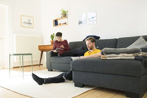 Casual couple relaxing in living room at home - SBOF01789