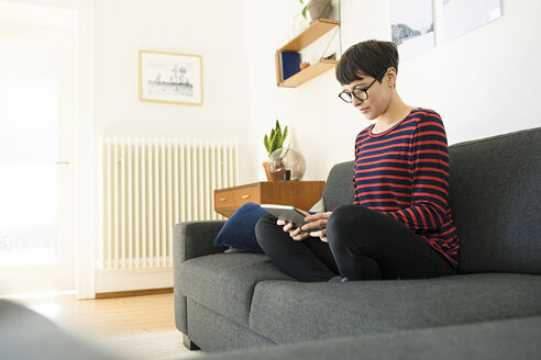 casual short-haired woman relaxing on lounge couch in her modern living room using a tablet - SBOF01792