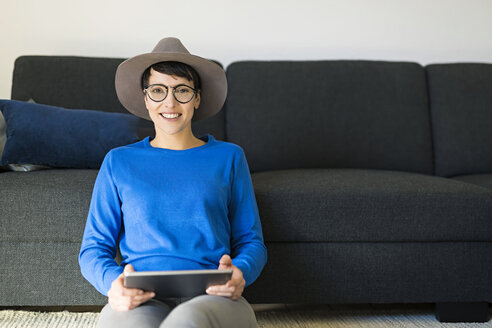 Portrait of smiling woman in living room using a tablet - SBOF01795